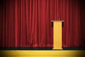 Rostrum with microphone and red curtain waiting for speech.